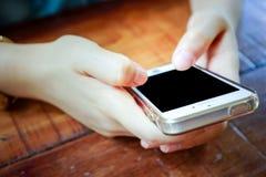 2 manos que sostienen el teléfono elegante móvil con la pantalla en blanco Fotografía de archivo
