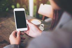 Manos que sostienen el teléfono móvil blanco con la pantalla blanca en blanco con la taza de café caliente en la tabla de madera  Imágenes de archivo libres de regalías