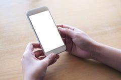 Manos que sostienen el teléfono móvil blanco con la pantalla de escritorio en blanco en la tabla en café Foto de archivo