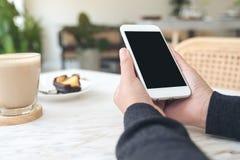 Manos que sostienen el teléfono móvil blanco con la pantalla negra en blanco con una taza de café y de bocado en la tabla en café Fotografía de archivo