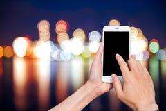 Manos que sostienen el teléfono móvil con la pantalla en blanco del espacio de la copia Fotografía de archivo libre de regalías