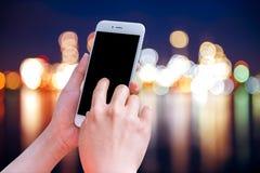Manos que sostienen el teléfono móvil con la pantalla en blanco del espacio de la copia Imagenes de archivo