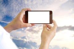 Manos que sostienen el teléfono móvil de la pantalla en blanco con el fondo del cielo azul Fotografía de archivo libre de regalías