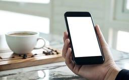 Manos que sostienen el teléfono móvil negro con la pantalla blanca en blanco con una taza de café en café Imagenes de archivo