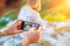 Manos que sostienen el teléfono y que toman las imágenes de la muchacha en el teléfono imagen de archivo libre de regalías