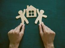 Manos que sostienen hombres y la casa de madera imagen de archivo libre de regalías