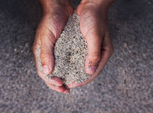 Manos que sostienen la arena Imagen de archivo
