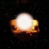 Manos que sostienen la bola de cristal que brilla intensamente Foto de archivo
