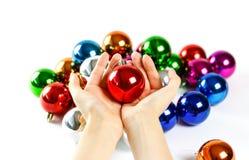 Manos que sostienen la bola de la Navidad En el fondo de muchos Christma Foto de archivo