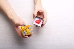 Manos que sostienen la caja de regalo con poco corazón Fotografía de archivo