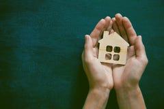 Manos que sostienen la casa de madera imagen de archivo libre de regalías