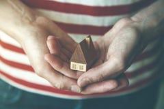 Manos que sostienen la casa de madera cuidadosamente imágenes de archivo libres de regalías