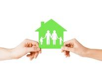 Manos que sostienen la casa verde con la familia Imagen de archivo