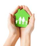 Manos que sostienen la casa verde con la familia Fotografía de archivo libre de regalías