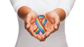 Manos que sostienen la cinta de la conciencia del orgullo gay del arco iris fotografía de archivo libre de regalías