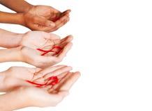 Manos que sostienen la cinta del SIDA Foto de archivo libre de regalías