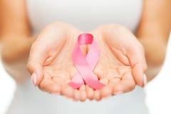 Manos que sostienen la cinta rosada de la conciencia del cáncer de pecho Fotografía de archivo