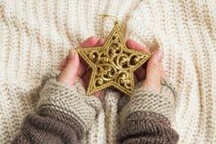 Manos que sostienen la decoración de oro de la estrella del brillo de la Navidad Fotografía de archivo libre de regalías