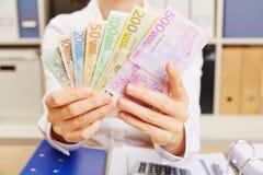 Manos que sostienen la fan euro del dinero Imagen de archivo libre de regalías