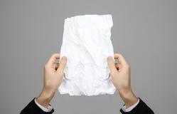Manos que sostienen la hoja arrugada del papel A4 en backg gris Fotos de archivo