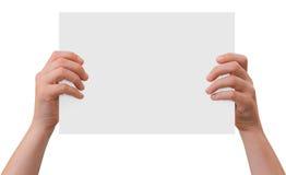 Manos que sostienen la hoja en blanco del papel Foto de archivo