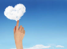 Manos que sostienen la nube en forma de corazón y el cielo azul Fotos de archivo libres de regalías
