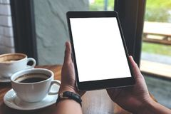 Manos que sostienen la PC negra de la tableta con la pantalla en blanco y las tazas de café blancas en la tabla Fotografía de archivo libre de regalías