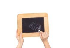 Manos que sostienen la pizarra con la foto de la flor aislada en blanco fotografía de archivo libre de regalías