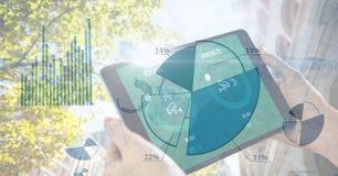 Manos que sostienen la tableta digital con la capa del gráfico de sectores Fotografía de archivo libre de regalías
