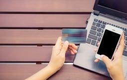 Manos que sostienen la tarjeta de crédito, teléfono elegante y usando el ordenador portátil Foto de archivo