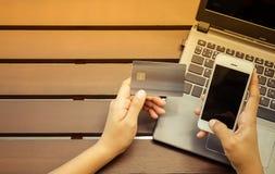 Manos que sostienen la tarjeta de crédito, teléfono elegante y usando el ordenador portátil Fotos de archivo