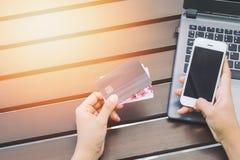 Manos que sostienen la tarjeta de crédito, teléfono elegante y usando el ordenador portátil Imagenes de archivo