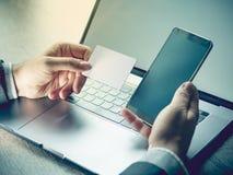 Manos que sostienen la tarjeta de crédito, teléfono móvil y usando el ordenador portátil Compras en línea, concepto de la reserva foto de archivo