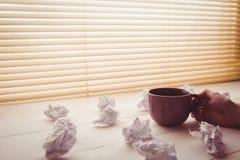 Manos que sostienen la taza de café al lado de las bolas de papel Foto de archivo