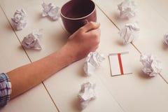 Manos que sostienen la taza de café al lado de las bolas de papel y de nota pegajosa Foto de archivo