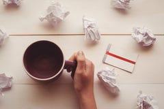 Manos que sostienen la taza de café al lado de las bolas de papel y de nota pegajosa Fotografía de archivo libre de regalías