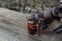 Manos que sostienen la taza de vino reflexionado sobre imagenes de archivo