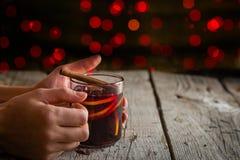 Manos que sostienen la taza de vino reflexionado sobre fotografía de archivo