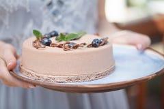 Manos que sostienen la torta cremosa deliciosa Fotos de archivo