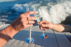 Manos que sostienen las copas de vino para tintinear Fotos de archivo libres de regalías