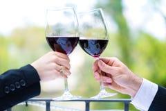 Manos que sostienen las copas de vino rojas para tintinear Foto de archivo libre de regalías