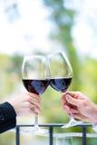 Manos que sostienen las copas de vino rojas para tintinear Imágenes de archivo libres de regalías