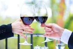 Manos que sostienen las copas de vino rojas para tintinear Imagen de archivo libre de regalías