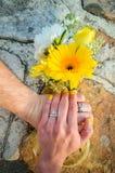 Manos que sostienen las flores con los anillos de bodas Fotos de archivo