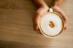Manos que sostienen las tazas de café del capuchino Fotografía de archivo libre de regalías