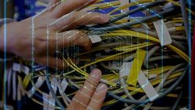 Manos que sostienen los cables con las líneas de código del hexágono entonces almacen de video