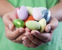 Manos que sostienen los huevos de Pascua Imagenes de archivo