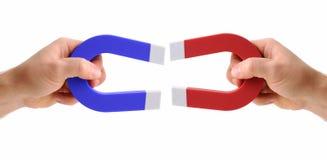 Manos que sostienen los imanes uno rojo y un azul Fotografía de archivo libre de regalías