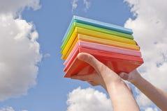 Manos que sostienen los libros del color Fotos de archivo libres de regalías