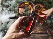 Manos que sostienen los vidrios con el vino reflexionado sobre para la Navidad y el período festivo imagen de archivo libre de regalías